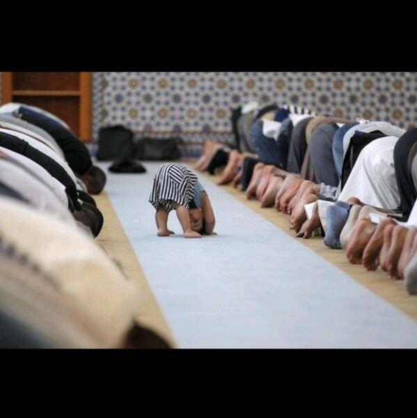 الصورة لطفل يقوم بتقليد المصلين