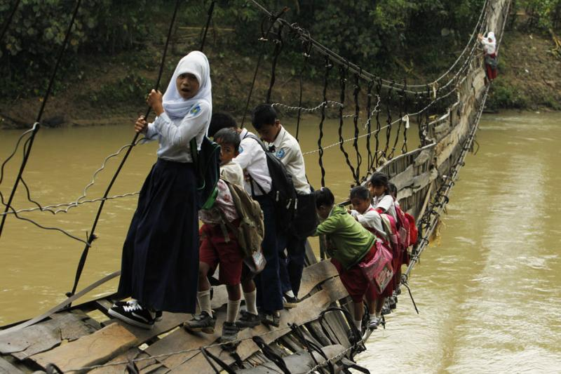 Students hold on to the side steel bars of a collapsed bridge as they cross a river to get to school