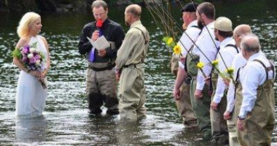 بالصورة... عروسان أمريكيان يتزوجان وسط نهر ملىء بأسماك السلمون