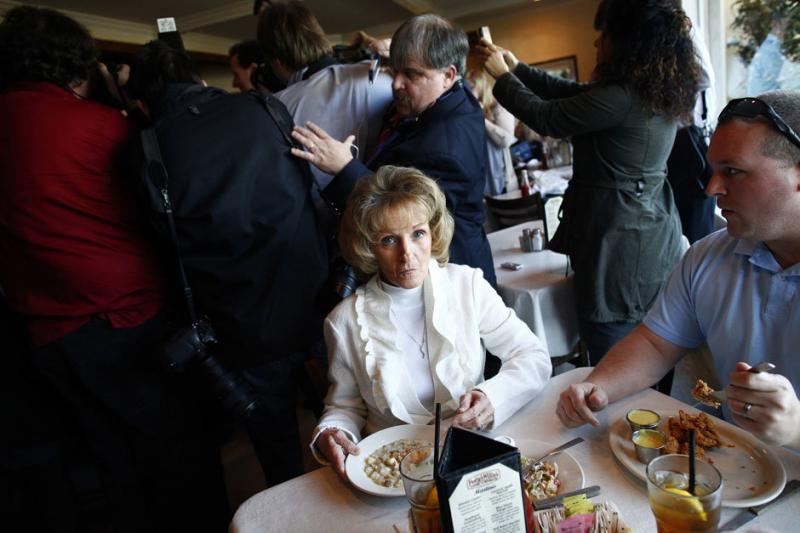 A woman eats clam chowder as media and supporters surround presidential candidate Rick Santorum