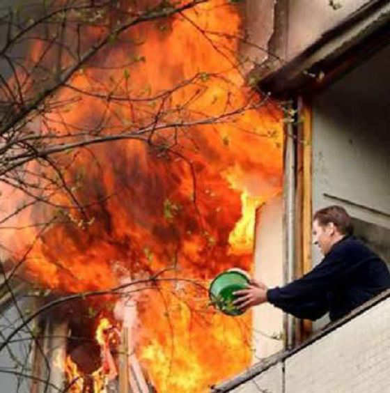 رجل يحاول إطفاء حريق بصحن ماء