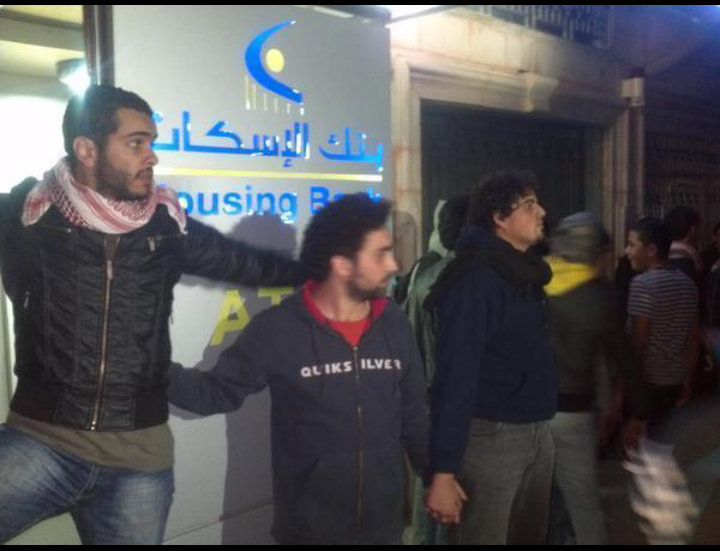 متظاهرين في #عمان #الأردن يشكلون درعاً بشرياً لحماية أحد فروع البنوك