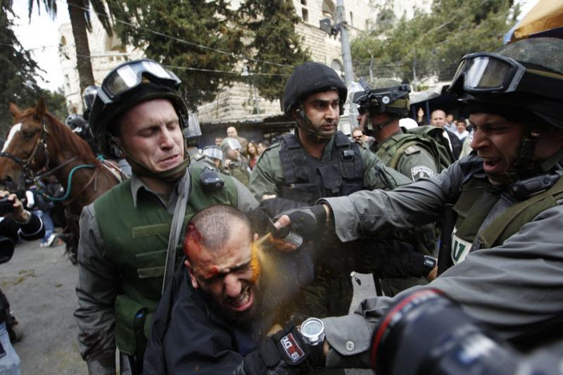 Israeli border police officers use pepper spray as they detain an injured Palestinian protester
