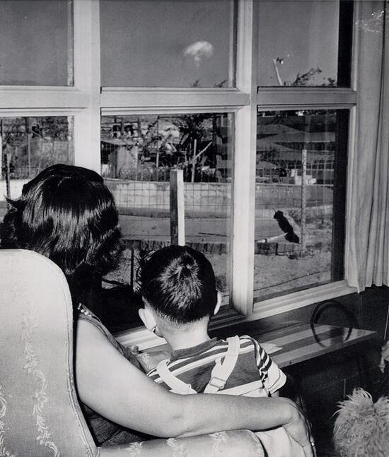 A mom and her son in Las Vegas watch the mushroom cloud after an atomic test 75 miles away. 1953