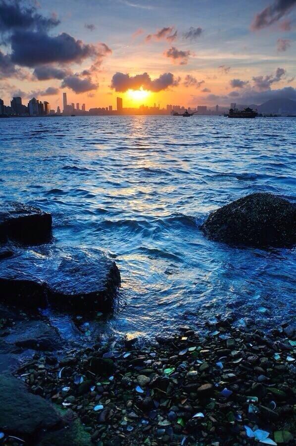 لحظة غروب الشمس في ميناء فيكتوريا في هونج كونج .