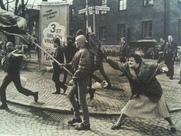 A woman hitting a skinhead with her handbag, Sweden, 1985. The woman was reportedly a concentration