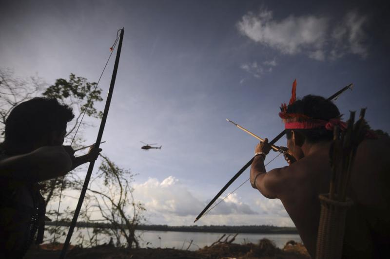 Indigenous people point their bows and arrows at a police helicopter