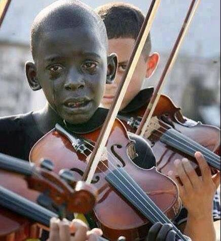 This child played a violin at his teacher's funeral. That teacher helped him escape poverty & violen