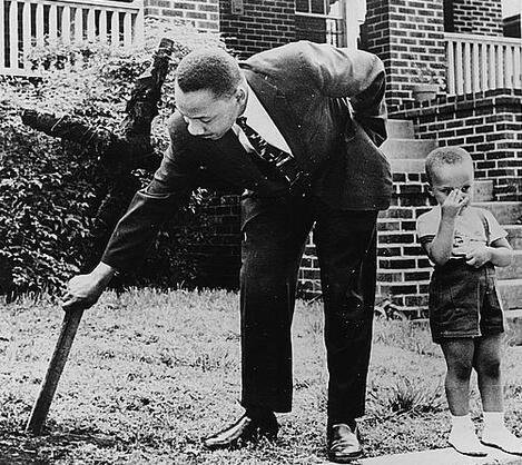 Martin Luther King Jr removing a burned cross from his front yard with his son at his side in 1960