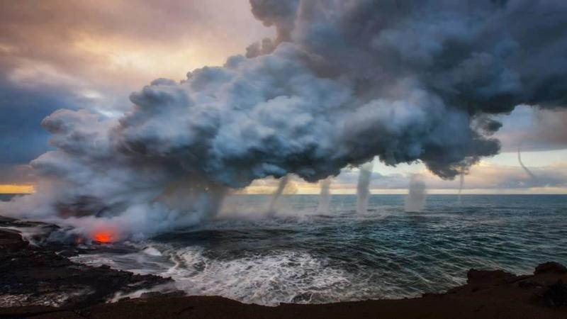 Multiple waterspouts touching down where the lava flow meets the ocean at Kilauea