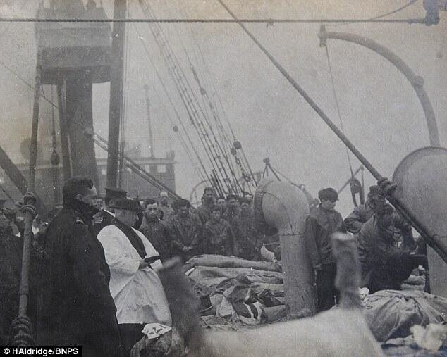 Rare photo shows a priest praying over Titanic victims before they are buried at sea. 1912