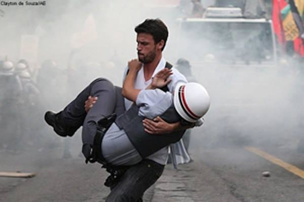 Brazilian protester carrying a cop that was hurt during the riots in Sao Paulo