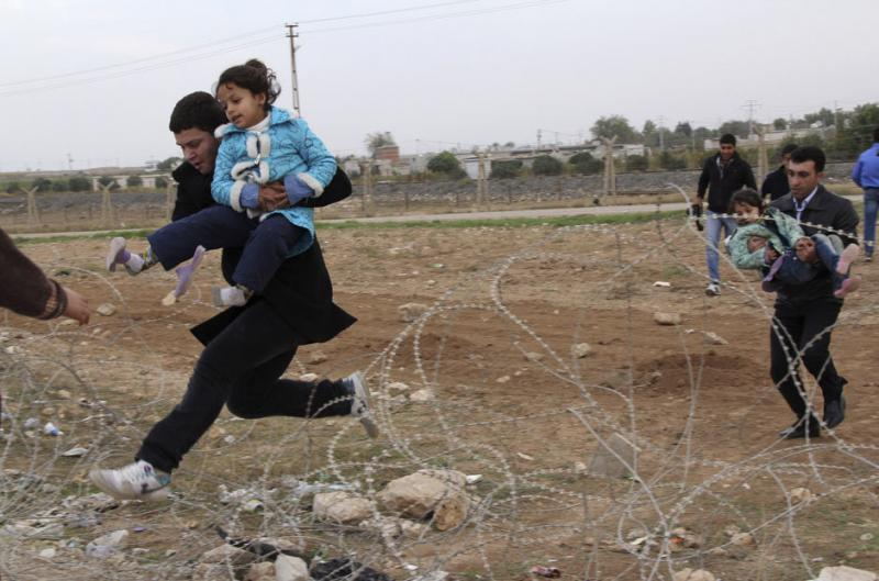 Syrians jump over barbed wire as they flee from the Syrian town of Ras al-Ain to the Turkish border