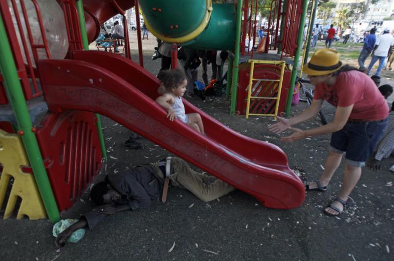 A Sudanese migrant sleeps under a slide as an Israeli girl slides down it at Levinsky park