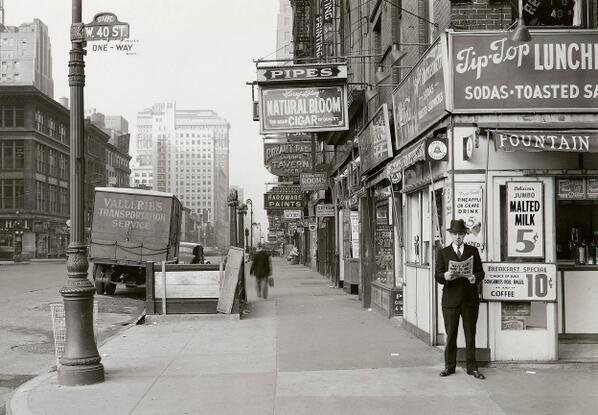 """New York man reads a newspaper, headline reads \""""Nazi Army Now 75 Miles From Paris.\"""". May 18, 1940"""