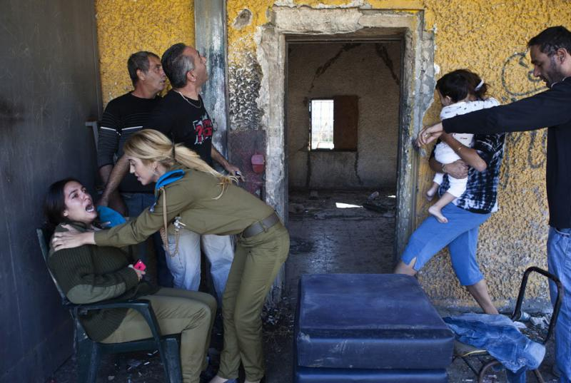 Israelis react and run for cover as a siren sounds warning of incoming rockets
