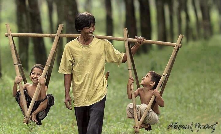 """طفلين مبتهجين على كتفي والدهم \""""السعادة لا تعني كثرة المال، يمكن أن تصنع السعادة بالقليل من الرضا""""!"""