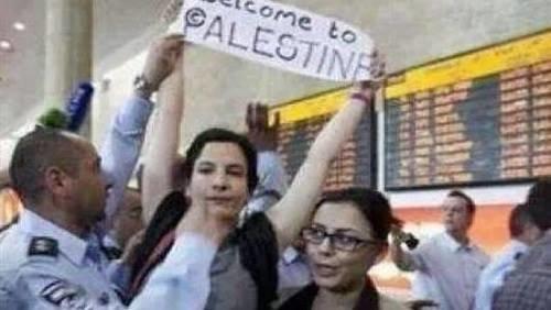 """صورة لفتاة أمريكية قامت برفع لافتة كتب عليها \""""مرحبًا بكم في فلسطين\""""، وذلك أثناء نزولها إلى مطار \""""تل أبيب"""
