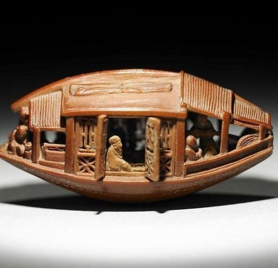 فنان صيني ينحت قارب على بذرة زيتون