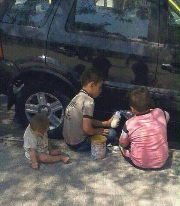 صورة طفل سوري يعد الحليب لإطعام أخيه الرضيع