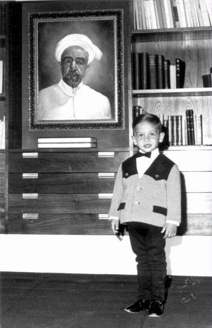 جلالة الملك عبد الله الثاني بن الحسين -عندما كان أميراً -، يقف إلى جانب صورة المغفور له الملك المؤسس عبد الله بن الحسين - طيب الله ثراه