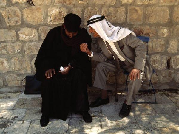 عجوز مسيحي فلسطيني وراهب اثيوبي يتبادلان الحديث بجوار الكنيسة في #القدس #فلسطين