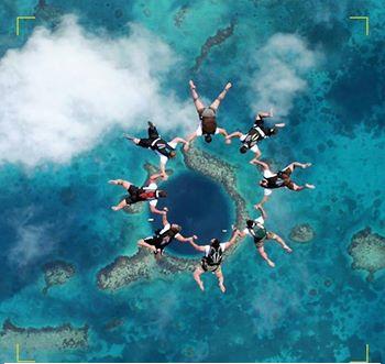 صورة مدهشة القفز بالمظلات بأتجاه حفرة بليز الزرقاء الغامضة في أمريكا الوسطى.