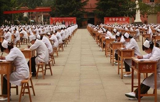 صورة مئات الطالبات الصينيات يؤدين اختبارهن في ملعب كبير مفتوح بلا أي مراقب !