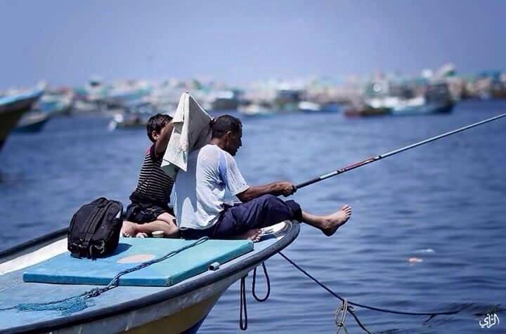 طفل من #غزة يظلل رأس أبيه الصياد ليحميه من حرارة الشمس