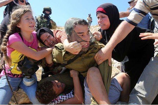 فتيات فلسطينيات يدافعن عن طفل يحاول جندي اسرائيلي القبض عليه - صورة ٥