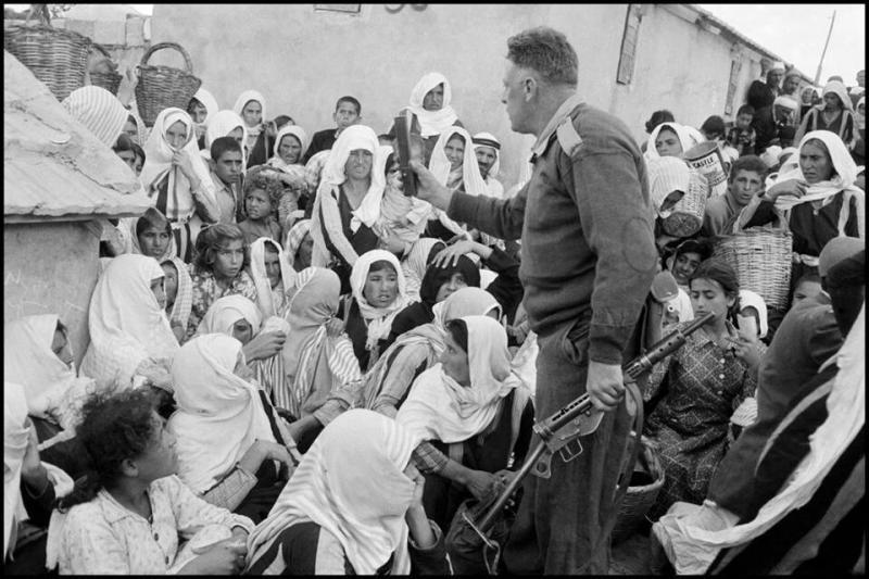 فلسطينيات في مخيم للاجئين في مدينة غزة ويظهر في الصورة جندي إسرائيلي يعطي التعليمات لهن. الصورة عام 1956