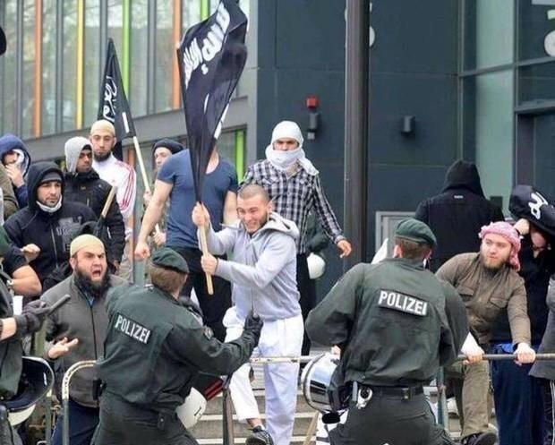 صورة لمتظاهرين يحملون علم #داعش تم نسبها لمهاجرين سوريين - زورا -لمنعهم من دخول أوروبا