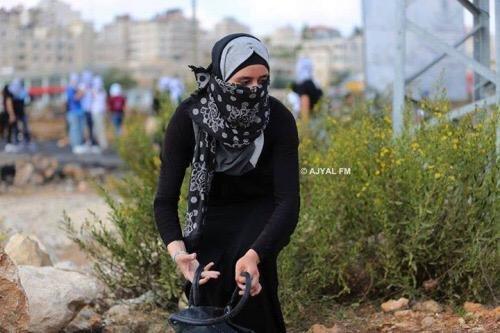 فتاة تجمع الحجارة للشبان داخل حقيبة يدها لإيصالها لهم في المواجهات الدائرة على المدخل الشمالي لمدينة البيرة. #فلسطين #انتفاضه_القدس -2