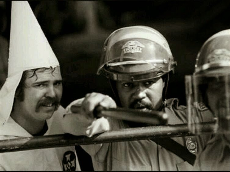 A black police officer protects a member of the KKK during a rally in 1983 #History