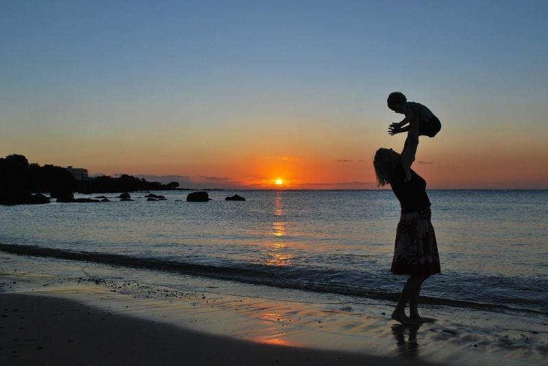 صور تحتوي #أم #تلعب #سعيدة #شاطئ_بحر #له #طفل #غروب_الشمس